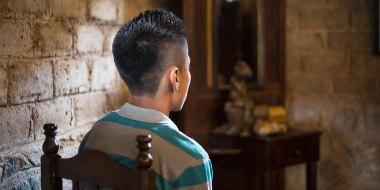 A young boy from El Salvador looks towards a window, his face hidden from view. The boy and his family were forced from their home when a gang threatened their lives.    *Name changed for protection. Photo credit: Tom Pilston/Save the Children, May 2017.