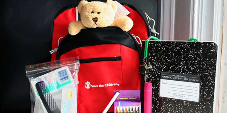 Emergency go-bag filled with teddy bear. school supplies and hygiene items.