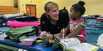 Sarah Thompson, Director of Preparedness for Save the Children, colors with a 2-year-old girl at a shelter in Jacksonville, Florida. Save the Children distributed cribs, infant hygiene supplies and activities to families in the aftermath of Hurricane Irma. Photo credit: Sara Neumann/Save the Children, September 2017.