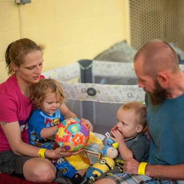 Shelby and Nick play with their children, two-year-old Sarah* and one-year-old Aaron*, on their cot in a shelter in San Antonio, Texas, on August, 27, 2017. The family has been in the shelter now for four nights. They evacuated from Rockport where Hurricane Harvey made land fall. They have lost everything. Save the Children distributed a variety of baby items to shelters in the San Antonio area including the cribs for Sarah* and Aaron*. *Names changed. Photo Credit: Susan Warner/Save the Children 2017.