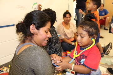 Anthony, 2, holds a toy stethoscope up to his mom, Beny, at a safe play space Save the Children established in an evacuation center in the Raleigh-Durham area in North Carolina as Hurricane Florence begins to make landfall in the Carolinas. Photo by Jeremy Soulliere for Save the Children.