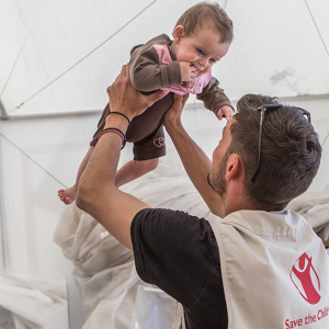 A worker holds a child in a Save the Children tent