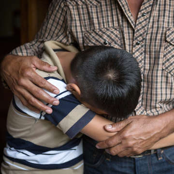 An El Salvadorian father comforts his 12-year old son. The boy lost his older brother to gang violence and the family cannot return home as a result. Save the Children is gravely concerned about the treatment and well-being of children from Central America and Mexico who are in the custody of the United States government after crossing the U.S.-Mexico border. Photo credit: Tom Pilston / Save the Children, May 2017