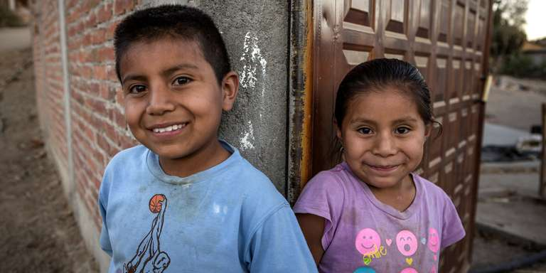 Nine-year-old Rodrigo is shown leaning in a doorway with his sister in Oaxaca, Mexico. Rodrigo was born in the U.S. His family migrated before he was born due to the lack of opportunities and poverty in its community in central Oaxaca. Now his family has returned in Oaxaca because his grandmother is sick. One day all the family wants to come back to USA. Save the Children runs programs that seek to prevent migration of unaccompanied children. One of the main focuses is to work on community roots and improve the living conditions for families. Photo credit: Jonathan Hyams / Save the Children, January 2017.