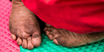 The tiny feet of a barefoot child resting on a colorful play mat in a child-friendly space are visible under a red blanket. The child's feet are covered in dirt. Some children and families crossing the U.S. border have walked for several days and have not bathed, are hungry, sick and exhausted. Save the Children is running child-friendly spaces and children's play areas at transit shelters in New Mexico for children once they leave detention facilities. Photo credit: Caroline Trutmann Marconi/ Save the Children, Nov 2018.