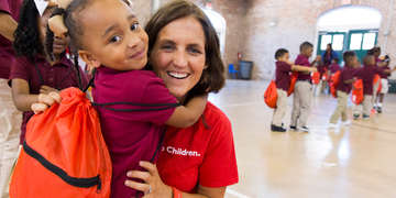 "Erin, Save the Children's Sr. Director for Emergency Preparedness, gets a hug from a child who received a backpack with disaster supplies at a special event in New Orleans on the anniversary of Hurricane Katrina. Save the Children holds ""Prep Rallys"" to teach kids how to prepare for disaster. Photo credit: Lee Celano/Save the Children, August 2015."