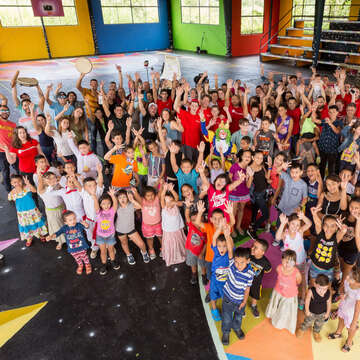A group photo of residents of Ciales, Puerto Rico as they celebrate their completion of a mural (by artist Okuda San Miguel) at a community basketball court. The project is part of Save the Children's long-term child resilience plan, as Ciales rebounds after Hurricane Maria in September 2017. Photo credit: Gabriel Gonzalez / Save the Children, December 2017.