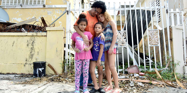 A grandmother embraces three of her grandchildren amid debris and rubble caused by Hurricane Maria. Like most families, they're coping with the realities of life and loss after the devastating storm in 2017. Photo credit: Rebecca Zilenziger / Save the Children, October 2017.
