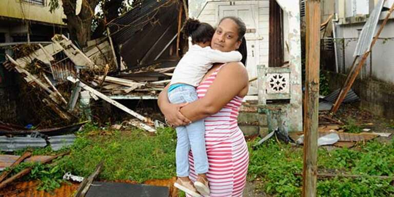 A mother holds her child and stands around destruction in Puerto Rico caused by Hurricane Maria.
