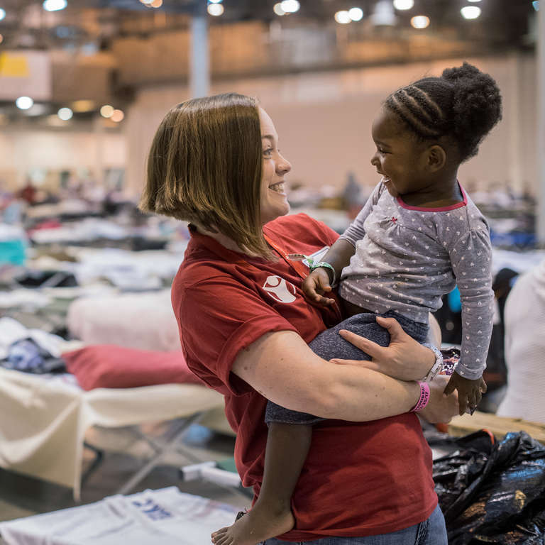 Erin, a Save the Children staff member, smiles at a 2-year old girl in a mega-shelter in Houston. Save the Children distributed cribs and other essentials to families in Texas in the aftermath of Hurricane Harvey. Photo credit: Susan Warner/Save the Children, September 2017.