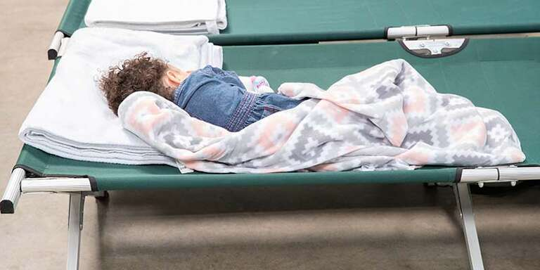 A young girl sleeps on a cot in a transit shelter at the U.S. Southern Border