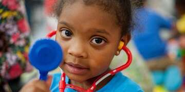 A young girl plays with a toy stethoscope.