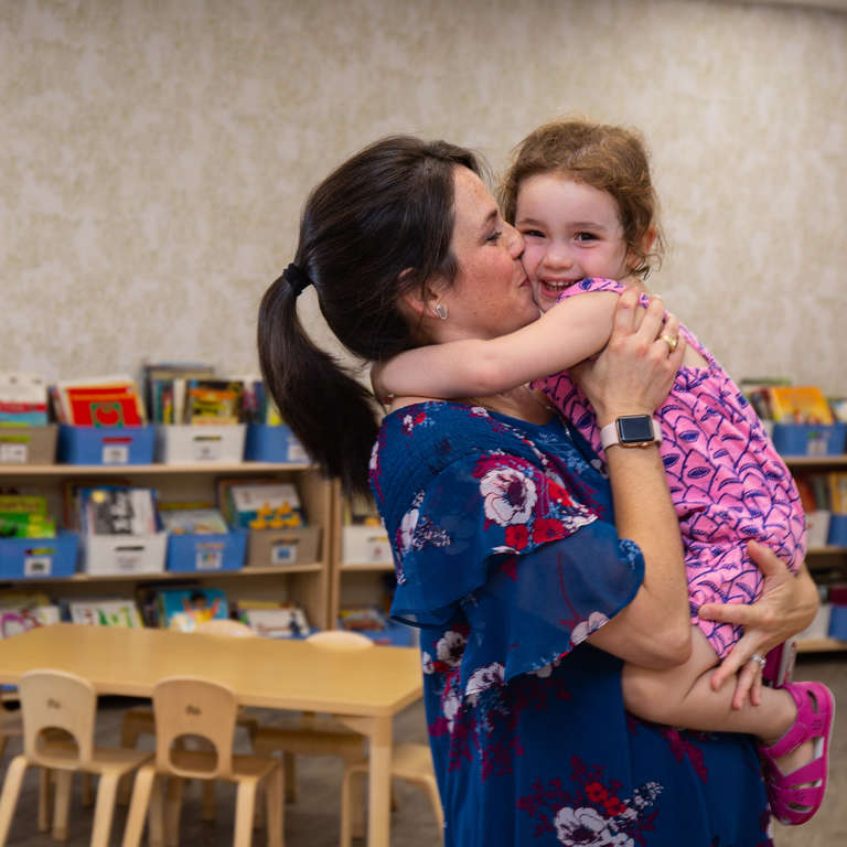 Marisa hugs her daughter Caley, 3, at her daycare in Texas. They're standing in a newly refurbished library that was destroyed in Hurricane Harvey, 2017. Save the Children funding helped rebuild the new library, as well as the daycare's infant and toddler playground, and occupational therapy gym. Save the Children, June 2018.