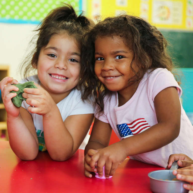 Two smiling children play with clay in Texas child care center classroom Save the Children helped to restore following Hurricane Harvey. Photo credit: Ellery Lamm / Save the Children