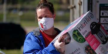 A woman in a Save the Children shirt and mask unloads an Instant Pot from a delivery truck