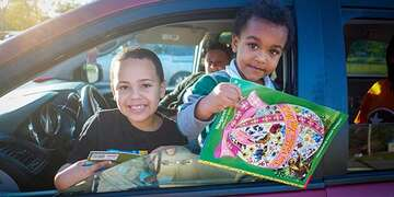 Two children hold educational games while smiling from the open window of their family car in Tennessee.