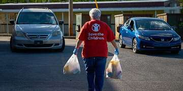 A woman in a Save the Children shirt carries a shopping bag of supplies in each arm.