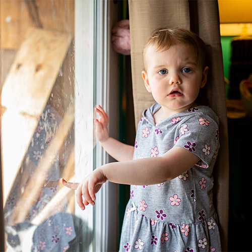 A two-year-old girl stands at a glass door with one hand against the glass in her home in West Virginia.