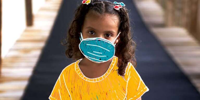 A young girl stands in the hallway of a school with a hand-drawn face mask covering her mouth and nose.