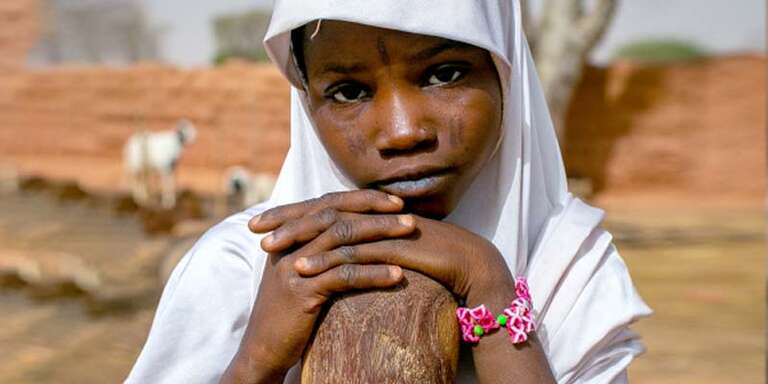 A young girl rests her hand on her knee.