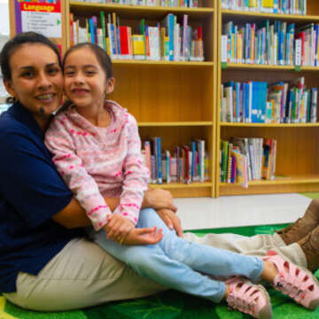 Consuelo sits with her mom, Luz, in the library at her southwest Florida child care center. Consuelo participated in Save the Children's Journey of Hope resilience program in the aftermath of Hurricane Irma, which helps children and caregivers cope with traumatic events, develop their natural resiliency and strengthen their social support networks. Journey of Hope has helped kids across the state of Florida cope with stress and anxiety following the catastrophic 2017 storm. Save the Children, June 2018.
