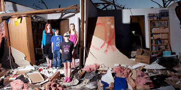 A group of children stands amid the debris that was once their grandmother's home after an EF5 tornado hit Moore, Oklahoma in May of 2013. Their parents are working to salvage what they can from the house. Pictured here are Randa, 14, Shelby, 16, Brett, 10 and Mykayla.9.  Photo credit: Justin Clemons / Getty Images, May 2013.