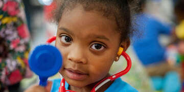 A 4-year old girl holds a pretend stethoscope.