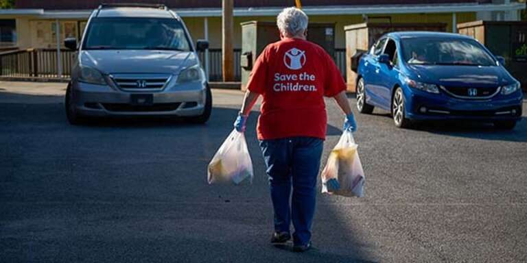 A woman walking away from the camera wears a Save the Children shirt and carries two plastic grocery bags.