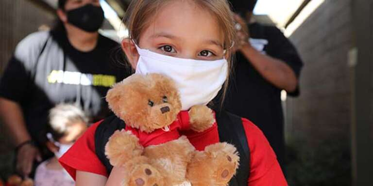 A young girl wears a white face mask while holding a toy teddy bear at a Save the Children distribution center.