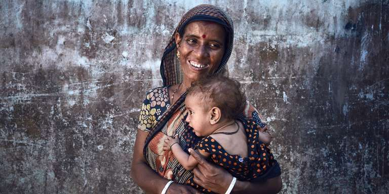 "A Bangladeshi mother, Shipra, is shown here with her daughter Prima, age 1. Shipra lives in a remote village a flood plain basin called a ""haor"" – it is surrounded by water for most of the year. The 400 villagers mainly work in agriculture, growing rice and vegetables, supplemented by fishing. Shipra, has had four babies but the first three died soon after they were born. Her son Nirob, 5, Prima (shown here) are her only surviving children. Shipra's husband Monto is blind in one eye (his eye is missing) and struggles to get work. This means the family can't afford to pay for healthcare. Thanks to Save the Children, a clinic was built close to their village, making it much easier for the family to receive proper healthcare. Photo credit: CJ Clarke / Save the Children, May 2016."