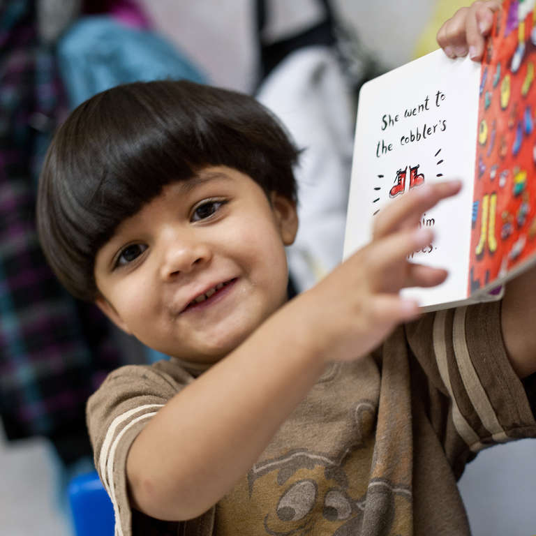 Three-year-old Victor enjoys a book during daycare. Photo Credit: Susan Warner