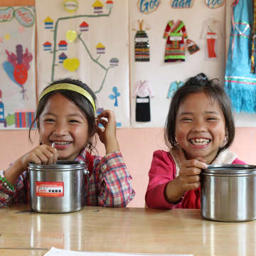 Two smiling schoolgirls in Vietnam eat lunch at a Save the Children-sponsored program. Photo Credit: Save the Children, July 2016.