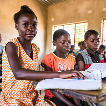 A 12-year old girl in Zambia sits in a classroom among other students. She participates in a basic education program made possible through sponsorship. Photo Credit: Victoria Zegler/Save the Children, October 2016.