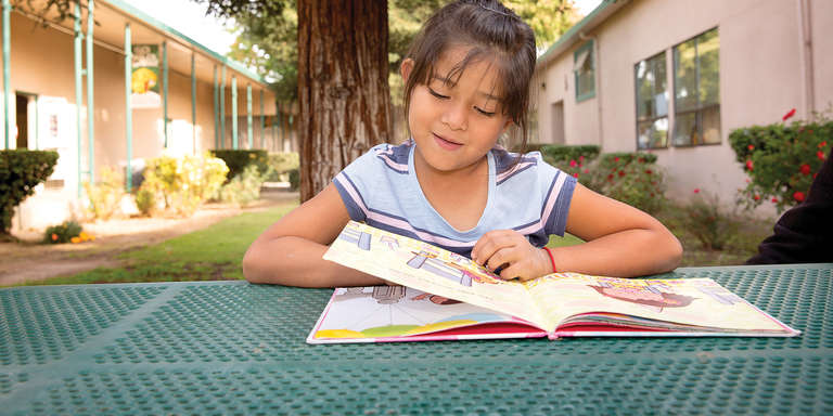 7-year-old Stephanie flips through the pages of a book during one of Save the Children's after-school programs in Central Valley, California. The program gives students opportunities to strengthen their literacy skills, get support with homework and participate in physical activities that combine fitness and fun. Photo credit: Tamar Levine/Save the Children, November 2017.