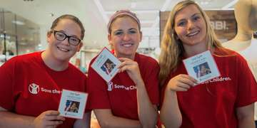Three volunteers wearing red Save the Children shirts and holding campaign cards gather together at a Save the Children store event.