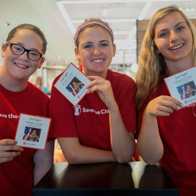 Three women wearing red Save the Children shirts and holding campaign cards gather together at a Save the Children store event. The women are volunteers helping to promote a campaign throughout the store. Photo credit: Susan Warner/Save the Children, July 2017.