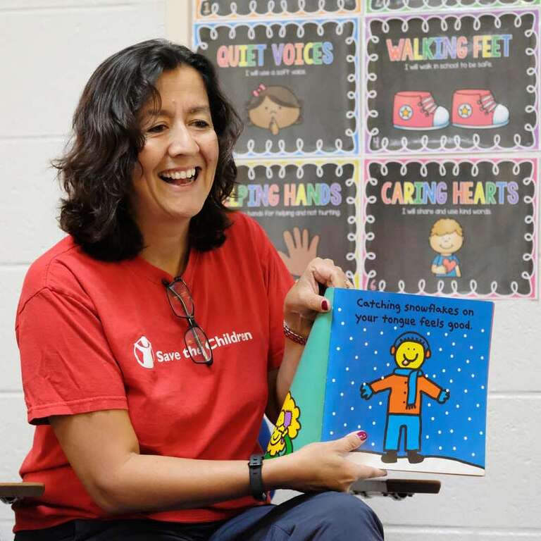 Janti Soeripto  President and CEO of Save the Children, holds a children's picture book.